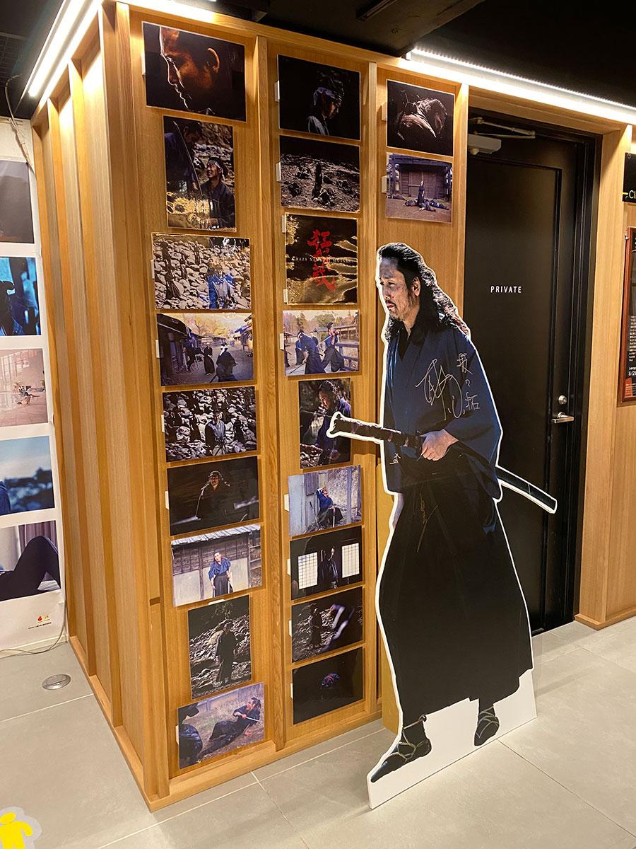 新宿シネマカリテの休憩スペースに展示された『狂武蔵』場面写真と、チケットが買えなかった坂口拓がせめても、とサインを残していったというスタンディ。
