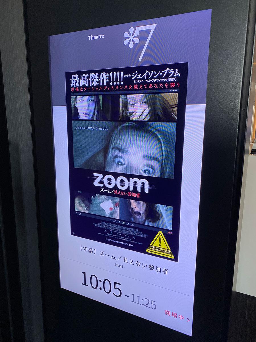 新宿ピカデリー、スクリーン7入口前のデジタルサイネージに表示された『ズーム/見えない参加者』キーヴィジュアル。
