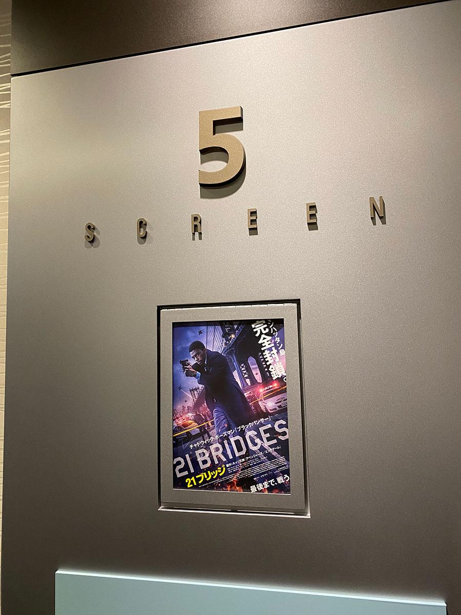 TOHOシネマズ上野、スクリーン5入口脇に掲示された『21ブリッジ』チラシ。